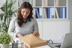 Business lady filling envelope with business documents