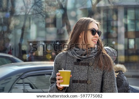 Stock Photo Business lady goes to work with a cup of coffee early in the morning on a busy street. She is dressed in a gray coat and gray scarf, she is in a good mood and she smiles, looking back