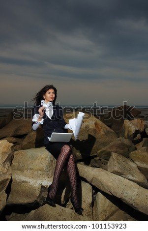 Business lady sitting on the rocks by the sea, against the backdrop of a cloudy sky.