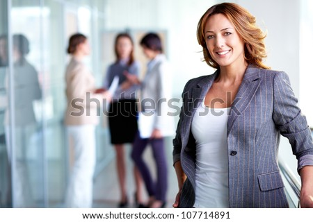 Business lady with positive look and cheerful smile posing for the camera