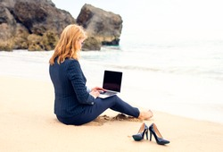 Business lady working with laptop computer on the beach
