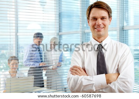 Business leader looking at camera with team of partners working in office behind