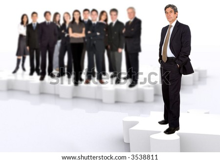 business leadership and teamwork with a businessman in front of a businessteam all standing on puzzle pieces - stock photo