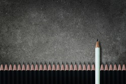 Business Leadership Concept : White pencil standing out from row of many black pencils on concrete background.