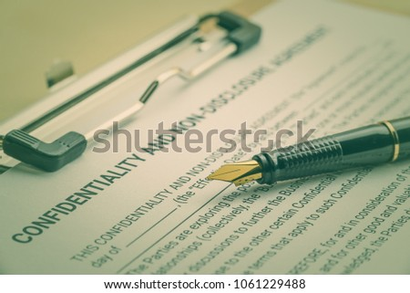 Business legal document concept : Fountain pen on a confidentiality and non disclosure agreement form. Confidentiality agreement is a legal contract between 2 parties that outlines confidential issues