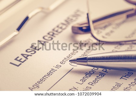 Business legal document concept : Pen and glasses on a lease agreement form. Lease agreement is a contract between a lessor and a lessee that allow lessee rights to use of a property owned by lessor Imagine de stoc ©