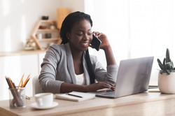 Business lifestyle. African Businesswoman Talking On Mobile Phone And Working With Laptop In Modern Office, Copy Space