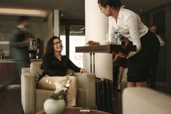 Business lounge staff serving coffee to female traveler at waiting area. Business woman waiting at airport departure lounge.