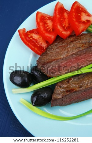 business lunch meat savory : grilled beef fillet mignon on blue plate with pepper chives and black greek olives over blue wooden table