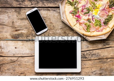 Business lunch mock up. Fast on-line delivery pizza. Top view image of Tablet PC, smartphone and Pizza