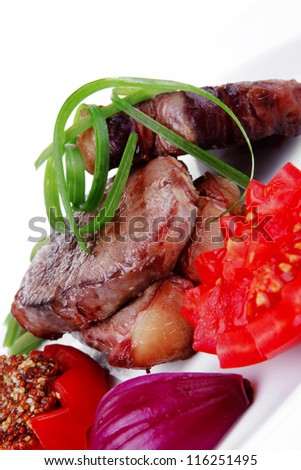 business lunch roasted beef meat strips steak on white ceramic plate with sweet pea and tomatoes isolated over white background