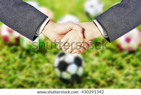 business ma hand shake with soccer blur background