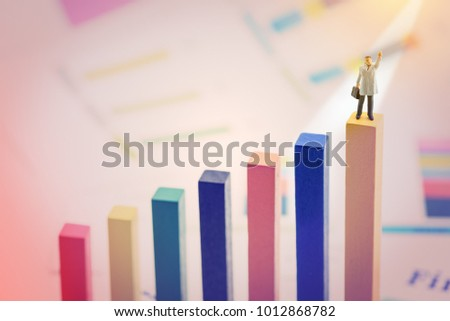 Business magnate or powerful personal business ownership concept : Miniature figurine businessman in a grey overcoat carries a briefcase, raises his left hand, stands on the first place wood pole. #1012868782