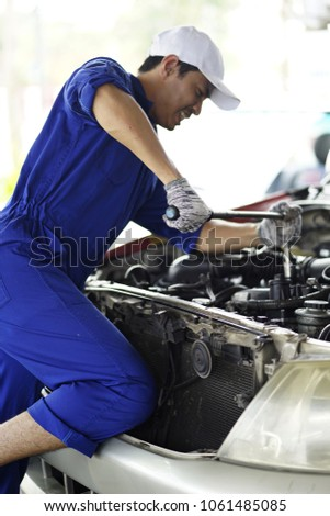 business  maintenance and people concept. Mechanic checking and fix car within garage. Young worker working in auto repair garage. Car maintenance. Hands of car mechanic repairing a car engine #1061485085
