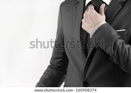 Business man adjusting his necktie. isolated on white