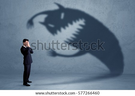 Business man afraid of his own shadow monster concept on grungy background #577266460