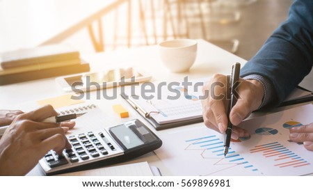 Business man analysis on data paper with business woman using calculator at the office
