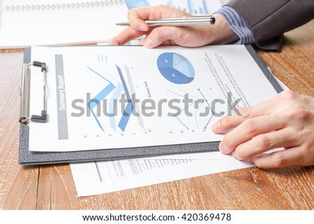 business man analyzing graph and chart document report, business performance concept #420369478