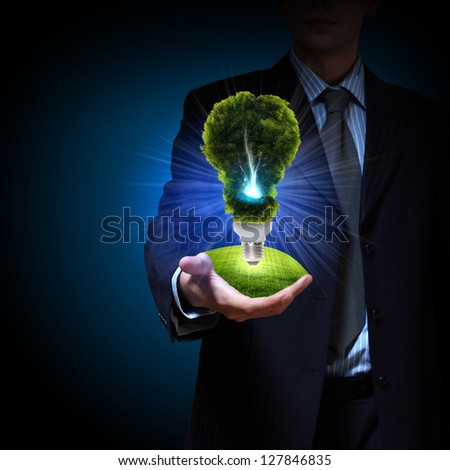 Business man and a light bulb as a symbol of green energy