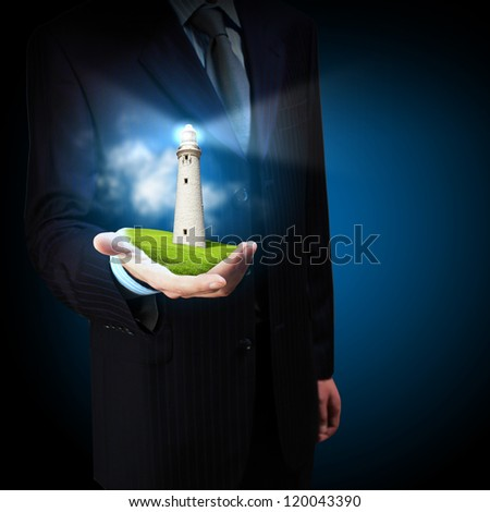 Business man and a lighthouse shining in darkness