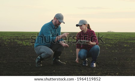 Business man and an agronomist are studying seedlings of crops in field. Business people teamwork. Farmers man, woman work in field with computer tablet. Smart farming technologies in agriculture