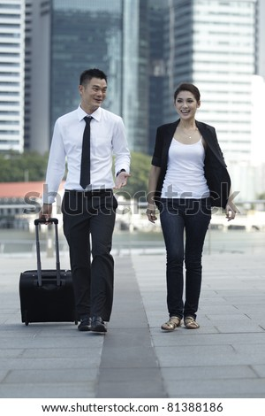 Business man and Business woman Walking with a wheeled Suitcase