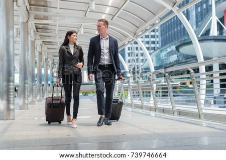 business man and business woman wear black suit walk together with luggage on the public street, business travel concept
