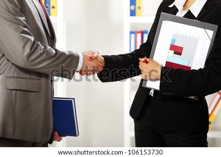 Business man and business women in the office she is standing and shaking hands close up