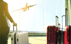 business man and stack of traveling luggage standing in airport terminal and passenger plane flying above