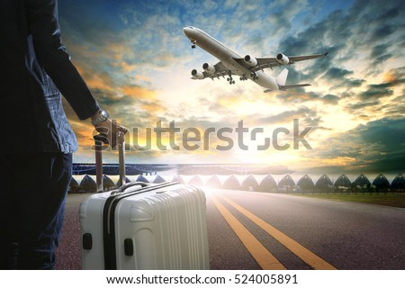 business man and traveling luggage standing in airport terminal and passenger plane flying over sky #524005891