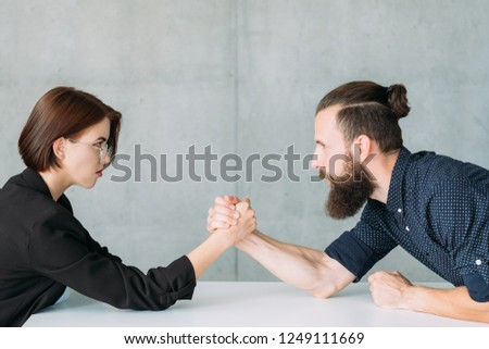business man and woman arm wrestling at table. competition rivalry and fighting. #1249111669