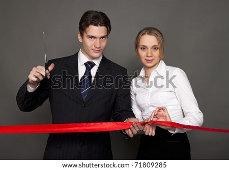 business man and woman cutting the red ribbon