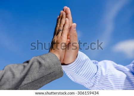 Business man and woman giving five, close up hands detail. Two hands clap together under blue sky.