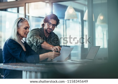 Business man and woman having a meeting in office. Two business colleagues discussing over a report document at work.