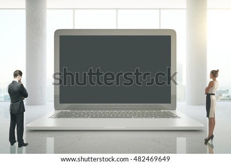 Business man and woman looking at abstract huge laptop screen in bright interior. Mock up, 3D Rendering