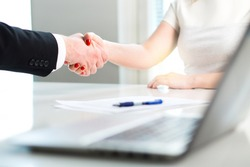 Business man and woman shaking hands after successful job interview or meeting. Young applicant making contract of employment. Employer hiring new employee. Handshake in office. Recruitment of intern.
