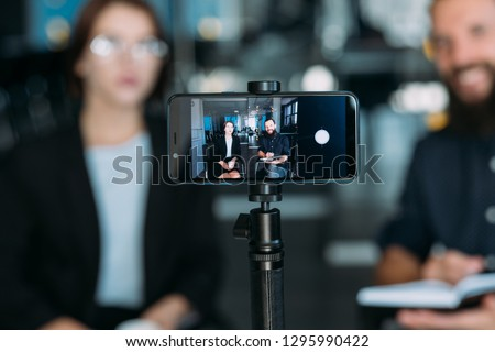 business man and woman shooting video using smartphone on tripod. coaching workshop
