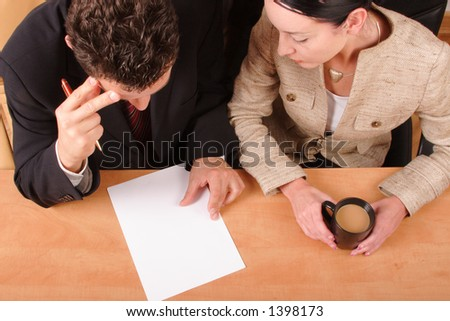 business man and woman sitting at the desk are reading paper. man holding pen, woman cup of white coffee