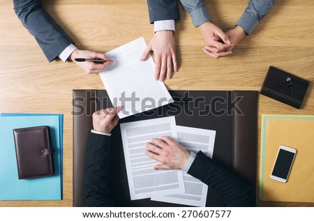 Business man and woman sitting at the lawyers\'s desk and signing important documents, hands top view, unrecognizable people