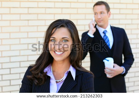 Business Man and Woman Team Smiling and Wearing Suits and Looking at the Camera