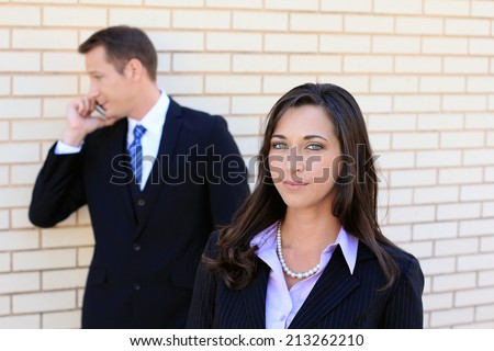 Business Man and Woman Team Smiling and Wearing Suits and Looking at the Camera While Working