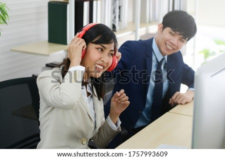 Business man and woman teasing to pull a headphones in during working hour in office