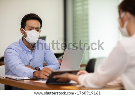Business man and woman wearing face mask meeting and working together for discussion and brainstrom to get ideas or marketing solution with social distance due COVID-19 virus flu pandemic and protect