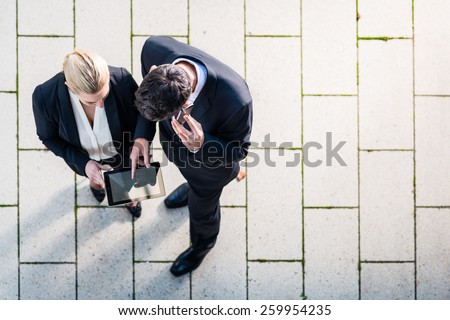 Business man and woman  with tablet computer standing on square, seen in top view stock photo