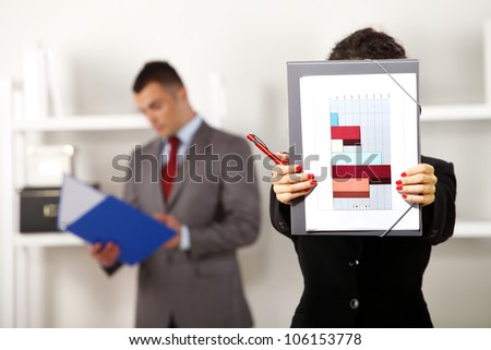 Business man and women standing and working in the office while she is holding folder with some charts in front of her face