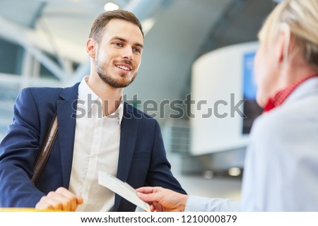 Business man as a passenger at the check-in counter during the air ticket check at the airport