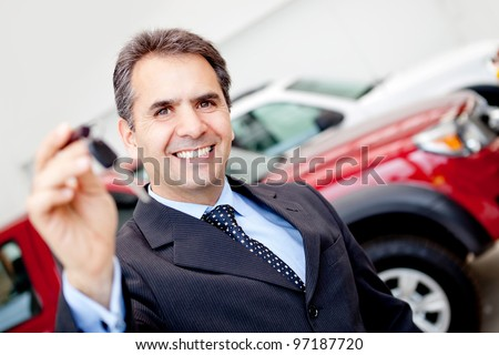 Business man at the dealership buying a car holding keys