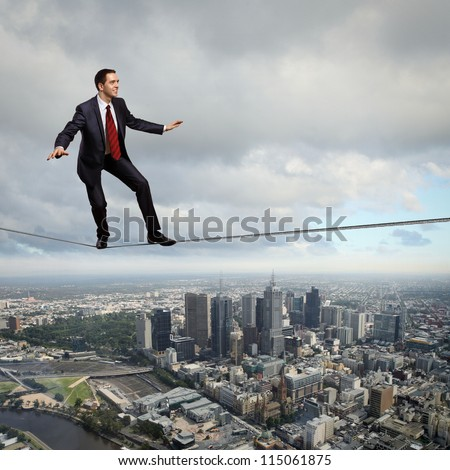 Business man balancing high over a cityscape