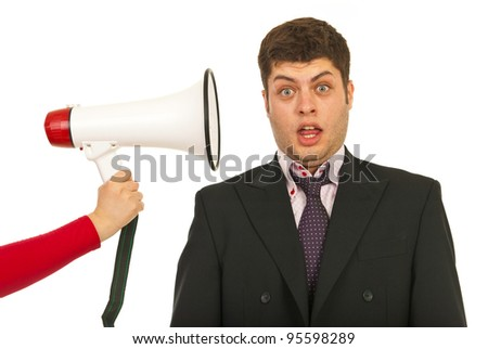 Business man being scared and surprised by megaphone shout isolated on white background
