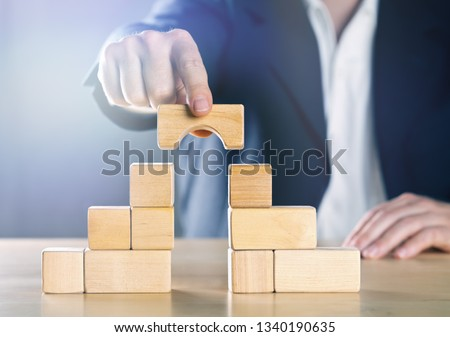 Business man bridging the gap between two towers or parties made from wooden blocks; conflict management or mediator concept, blue toned with ligth flare Foto stock ©